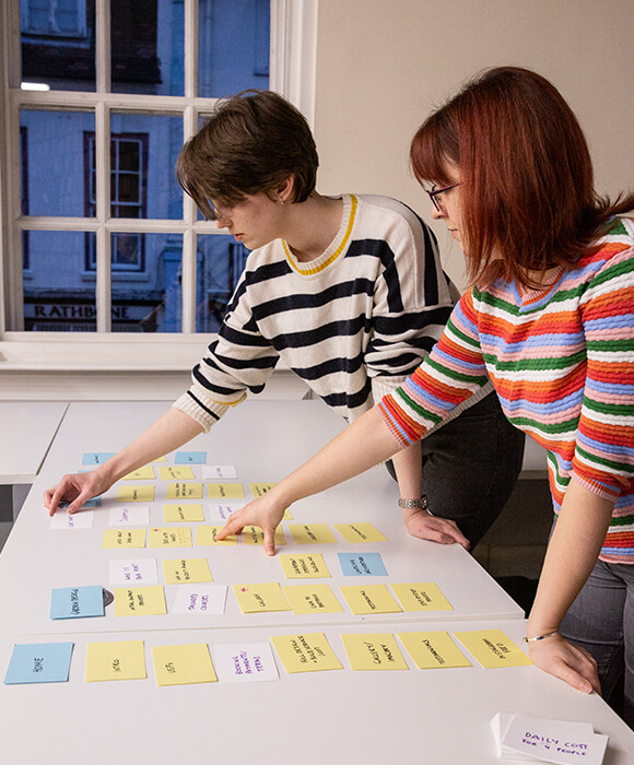 Two people sorting planning cards on a desk