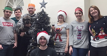 The Edge of the Web team celebrating around a christmas tree