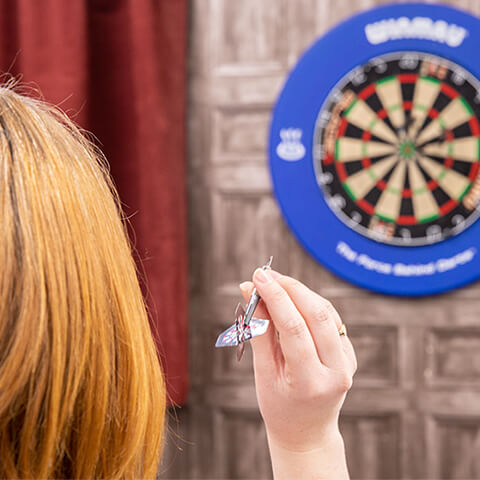 Team member about to throw dart at a dart board