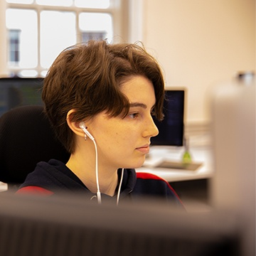 Front end developer coding with headphones in